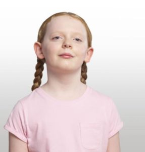 A blind girl stands against a white backdrop. She has red hair which is platted and is wearing a pink t-shirt
