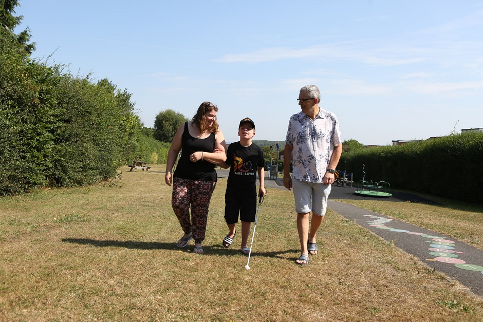A picture of a boy walking with his parents