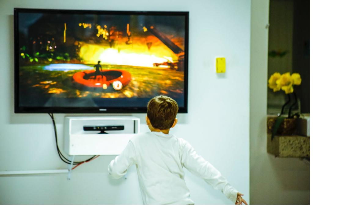 A boy looking at a mounted television