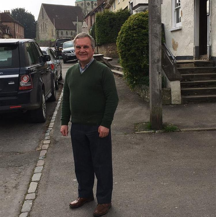 John stands in a village street with houses in the background