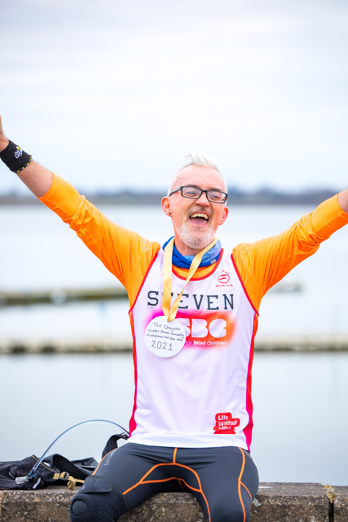 Steven is photographed holding his arms aloft and smiling, in front of the lake he ran around. He is wearing an RSBC running vest and has a homemade medal around his neck.