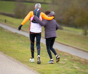 Steven is pictured on his run with a lady alongside him. They have an arm round each other in support.