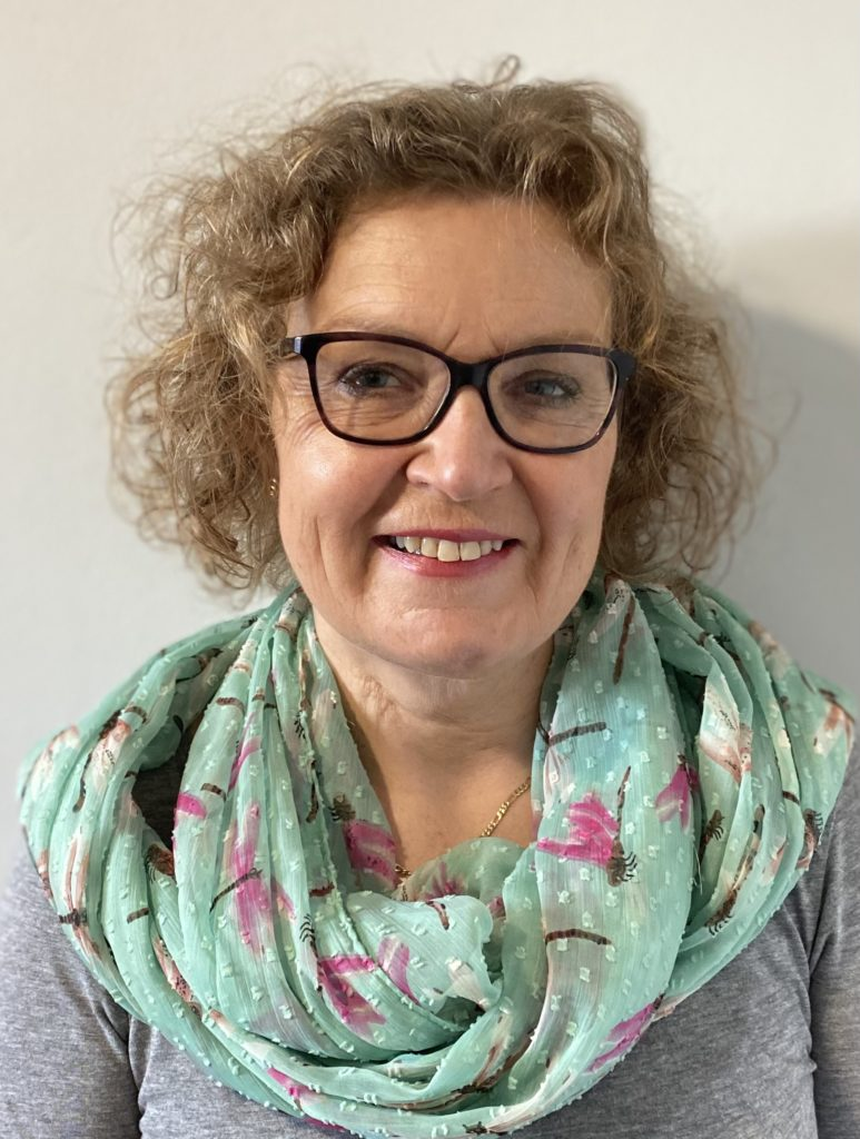 Sue Sharp standing against a white wall smiling, wearing glasses and a light blue flowery scarf
