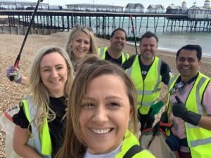 A group take a selfie on a beach with a pier in the background. They are wearing yellow hi vis jackets.