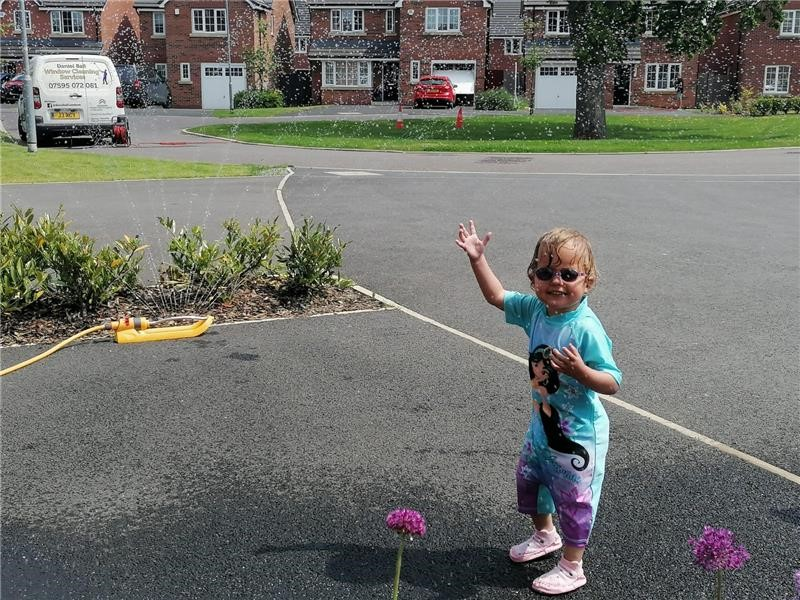 Anna standing on her driveway smiling and wearing glasses