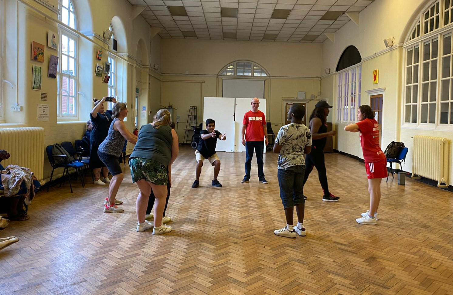 A group of young people standing spaced apart from each other as they have a dance session with an instructor.