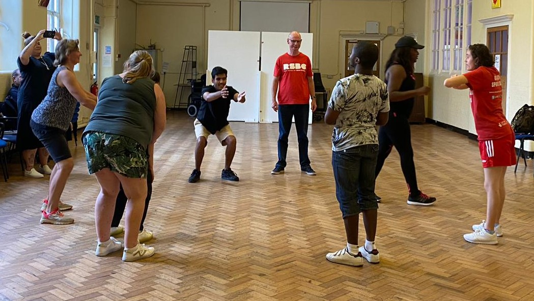 A group of young people participating in a dance session lead by a sports coach